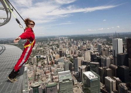 Canadian Press reporter Alex Posadzki leans over Toronto's downtown while participating in a media preview of EdgeWalk on the CN Tower on Wednesday, July 27, 2011.   (AP Photo/The Canadian Press, Darren Calabrese)